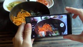 Tomar la foto de la comida del Bibimbap coreano tradicional del plato sirvió junto con pequeños acompañamientos clled banchan en  almacen de metraje de vídeo