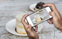 Tomar la foto de la comida, fotografía del postre por el teléfono elegante, torta de chocolate dulce con la salsa de la nata del  Foto de archivo