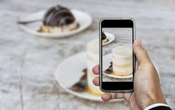 Tomar la foto de la comida, fotografía del postre por el teléfono elegante, torta de chocolate dulce con la salsa de la nata del  imagenes de archivo