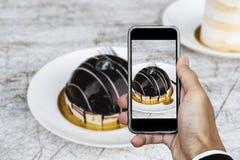 Tomar la foto de la comida, fotografía del postre por el teléfono elegante, torta de chocolate dulce oscura Foto de archivo libre de regalías