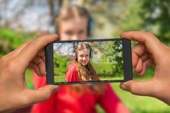 Tomar la foto de la señora que escucha la música con el teléfono móvil Imagen de archivo