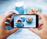 Tomar la foto de la taza de café por smartphone Foto de archivo libre de regalías