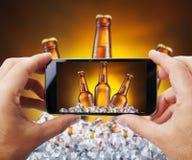 Tomar la foto de las botellas de cerveza en hielo por smartphone Fotografía de archivo libre de regalías