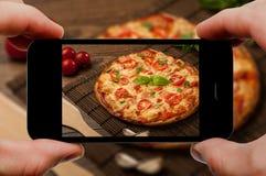 Tomar la foto de la pizza por smartphone Opinión del primer del proceso El fichero contiene las trayectorias de recortes para el  Imagenes de archivo