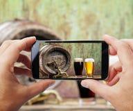 Tomar la foto de vidrios de cerveza por smartphone Imágenes de archivo libres de regalías