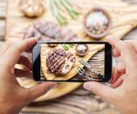 Tomar la foto del filete de carne de vaca por smartphone Foto de archivo libre de regalías