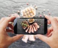 Tomar la foto del filete de carne de vaca por smartphone Fotos de archivo