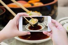 Tomar la foto del rollo de sushi en palillos Fotos de archivo