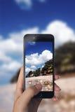 Tomar la imagen de la escena de la playa con el teléfono elegante Fotografía de archivo