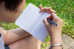 Tomar la nota con la pluma y el libro Fotos de archivo libres de regalías