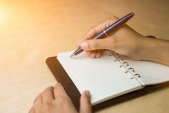 Tomar la nota sobre el cuaderno por la pluma de bola azul Fotografía de archivo