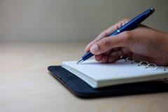 Tomar la nota sobre el cuaderno por la pluma de bola azul Foto de archivo