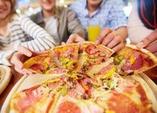Tomar la pizza Imagenes de archivo