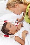 Tomar la temperatura del niño Imagen de archivo libre de regalías