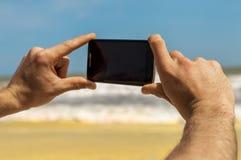 Tomar las fotos en el teléfono en el mar foto de archivo libre de regalías