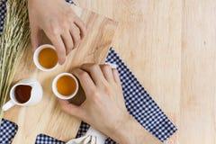Tomar las tazas de té en el fondo de madera de la textura Fotos de archivo libres de regalías