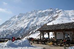 Tomar sol dos esquiadores exterior em um restaurante no Dolomit italiano Fotos de Stock Royalty Free