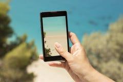 Tomar una foto de una playa hermosa con un teléfono móvil Foto de archivo libre de regalías