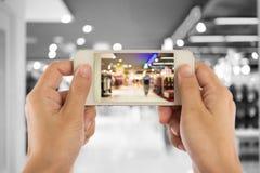 Tomar una imagen con un teléfono elegante en alameda de compras Imágenes de archivo libres de regalías