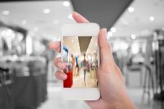 Tomar una imagen con un teléfono elegante en alameda de compras Fotografía de archivo libre de regalías