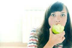 Tomar una mordedura de una manzana verde Foto de archivo libre de regalías