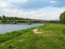 Tomas Masaryk Bridge Great Bridge across the Uzh River in Uzhhorod Ukraine. Embankment of the river with bright green young grass, water and a bridge - a stock photos