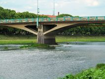 Tomas Masaryk Bridge in Uzhhorod close-up and people wade the river ford under it. The urban landscape of Uzhgorod with the shallow river Uzh and the Great royalty free stock photos
