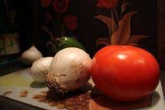 Tomat i företaget av vita lökar Royaltyfri Foto