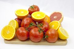 Tomat och apelsin på den vita bakgrunden med gröna blad på th royaltyfria bilder