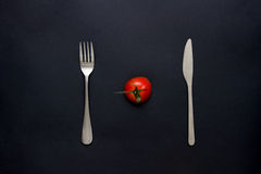 Tomat och bestick på tabellen Arkivbild
