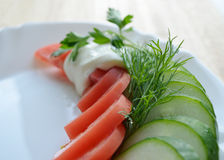 Tomat och gurka på den vita plattan Fotografering för Bildbyråer