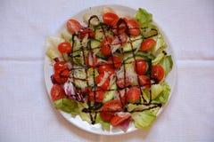 Tomat- och gurkasallad på en vit platta arkivfoton