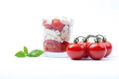 Tomat- och ostsallad i exponeringsglas, vit bakgrund Royaltyfria Foton