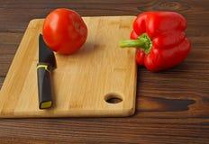 Tomat och spansk peppar på en bitande tabell fotografering för bildbyråer