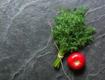Tomat och två grupper av gräsplan på en svart bakgrund arkivfoton