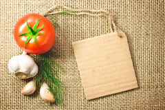Tomat och vitlökgrönsaker och prislapp på att plundra bakgrund Royaltyfri Foto
