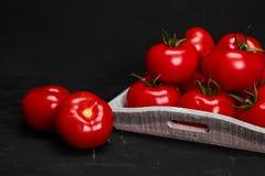 Tomat på en svart bakgrund med realistiska reflexions- och vattendroppar nya tomater Arkivfoton