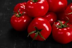 Tomat på en svart bakgrund med realistiska reflexions- och vattendroppar nya tomater Royaltyfria Bilder