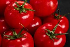 Tomat på en svart bakgrund med realistiska reflexions- och vattendroppar nya tomater Royaltyfri Foto