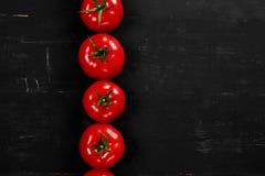 Tomat på en svart bakgrund med realistiska reflexions- och vattendroppar nya tomater Arkivbilder