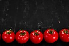Tomat på en svart bakgrund med realistiska reflexions- och vattendroppar nya tomater Arkivbild