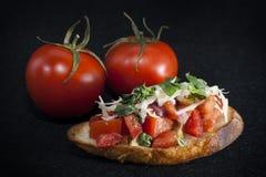 Tomatbruscheta på svart bakgrund arkivbild