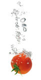 Tomate éclaboussant dans l'eau Images stock