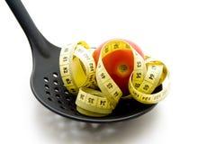Tomate auf Abstreicheisen mit Maßband Stockfoto