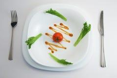 Tomate auf weißer Platte Stockbild