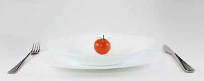 Tomate auf weißer Platte Lizenzfreie Stockbilder