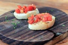 Tomate Bruschetta auf hölzerner Platte Stockbilder