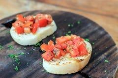 Tomate Bruschetta auf hölzerner Platte Lizenzfreie Stockfotografie