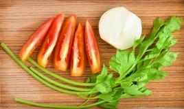 Tomate, céleri, oignon sur le plancher en bois Photographie stock libre de droits