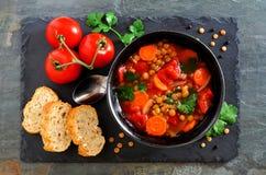 Tomate caseiro, sopa de lentilha, configuração lisa sobre a ardósia Fotos de Stock